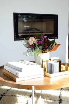Using a stack of books and a cluster of candles are easy ways to make your coffee table look stylish! Get all our coffee table styling tricks here!