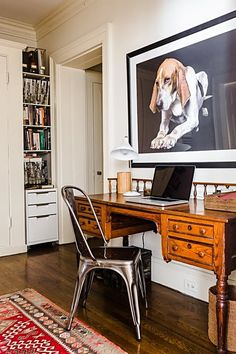 The office with a traditional wooden desk and patterned rug gets a modern pairing with a shiny metal chair.