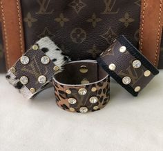 Cowhide cuffs with upcycled Louis Vuitton and stud/rhinestone embellishments. approximately wide. available in black, cheetah and natural cowhide patterns Easy on and off snaps. Louis Vuitton Necklace, Louis Vuitton Jewelry, Louis Vuitton Keychain, Louis Vuitton Monogram, Louis Vuitton Accessories, Louis Vuitton Handbags, Purses And Handbags, Louis Vuitton Vintage, Over Boots