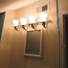 """Lauren of the blog """"The Starter Home Diaries"""" transformed her tiny attic bathroom with some paint and a Moen light fixture. Click photo to read more!"""
