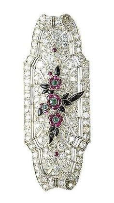 AN ART DECO RUBY, ONYX AND DIAMOND BROOCH  The tapered rectangular-shaped plaque set throughout with single and circular-cut diamonds, to the central floral motif set with ruby and emerald flowerheads and onyx leaves, mounted in platinum, circa 1925, 5.8 cm long by chrystal
