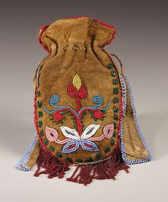 A BLACKFEET WOMAN'S BEADED HIDE POUCH AND PIPE. c. 1920. ... | Lot #77343 | Heritage Auctions
