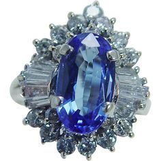 This beautiful estate ring is finely crafted in solid 14K Yellow gold and set with genuine Earth mined Tanzanite and diamonds. The center gem measures