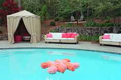 The couple's monogram is made of styrofoam and covered it in pink and orange carnations for this awesome floating pool decor.
