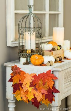 Fabulous fall décor doesn't have to cost a fortune. Learn how to make a custom table runner in just a few easy steps! 1) Cut linen fabric to desired length, trimming the raw edges.  2) Remove silk leaves from bushel and set aside. 3) Add trim or ribbon to the edges of the runner. 4) Begin layering leaves on each end of the runner, letting leaves hang off the edges.