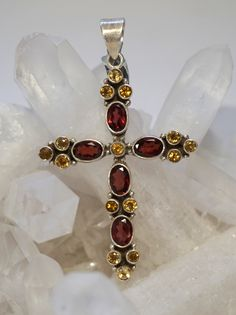 "5 Oval faceted Garnet gemstones, accented with 15 round faceted citrines, bezel-set in 925-hallmarked sterling silver. Length: 2.5"" with bail. Width: 1.5"""