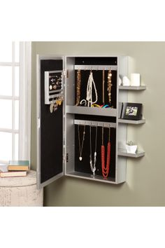 This is such a great idea! This jewelry armoire is mirrored on all sides and includes six mirrored shelves along the two outer edges. The beveled mirror front opens up and offers 14 hanging hooks, 16 earring notches, four cushioned ring holders, and a shelf with three bins for assorted pieces. The inside is lined with black felt to help protect all of your belongings from scuffing or scratching.