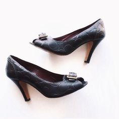 Coach Leather Embossed Signature C Pumps 100% authentic. Coach black leather heels with Signature C embossed design. Maroon leather insoles. White stitching. Peep toe. Buckle accent with brass hardware. Excellent used condition. Normal bottom wear and priced accordingly. PRICE FIRM. Coach Shoes Heels