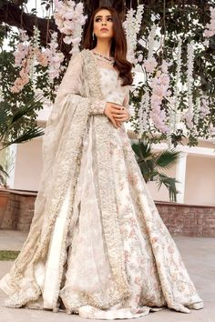 This ivory lehenga is in Dupion Silk fabric with dabka, sequins, kasab, beads zardozi embroidery. The blouse is in Silk fabric embellished with pearls, sequins. Dupatta is in Organza Silk with a four-sided embroidered border and gotta. Indian Wedding Gowns, Pakistani Wedding Outfits, Indian Bridal Outfits, Pakistani Bridal Dresses, Pakistani Wedding Dresses, Pakistani Dress Design, Indian Designer Outfits, Indian White Wedding Dress, Bridal Lenghas