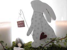 Ein süßer Hase, der mit seinen vielen kleinen Details eine wunderschöne Osterdekoration ist.  Er schmückt sich beidseitig mit Tupfen auf seinem Kleidchen und einem kleinem roten Herz.  Außerdem...