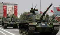 Turkish army tanks roll past a portrait of Mustafa Kemal Ataturk during a military parade in Ankara