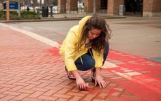 Delaney Cordova & Kent State University: The demonstration uses red sand in sidewalk cracks to represent those who have fallen through the cracks in our society. Those who are scarred and in plain sight but have no voice. Victims of human trafficking or modern day slavery. It's meant to be bright and eerie to spark people's curiosity that leads to them asking questions. The goal is to raise awareness and start a conversation to educate people on this tragedy that goes on in every country, every Sand Projects, Kent State University, Spark People, Human Trafficking, Curiosity, Conversation, Goal, Sidewalk, Bomber Jacket