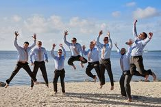 Excitement by the beachfront groomsmen'a attire black trousers light blue shirt ans pink tie without shoes at Key Largo Lighthouse Beach Wedding Venue in the Florida Keys