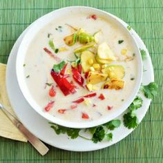 A creamy coconut soup infused with green curry, and garnished with peppers, corn, squash, and cilantro.