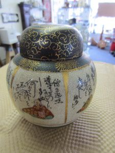 "Japanese Satsuma Ginger Jar - This week our ""Pick"" is another treasure from a far off country. It is a beautiful  hand painted Japanese Satsuma Ginger Jar. This lovely earthenware vessel is adorned with resting figures, Japanese text and gilding. While it is not antique it is a very attractive piece and shows the great skill of the artist who created it."