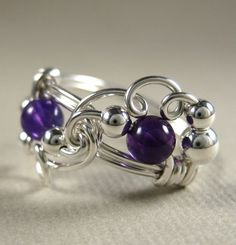 Beautiful wire wrapped ring in sterling silver and amethyst. I love the unique design! And amethyst is my birthstone :)