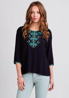 Perfected with rustic-charm, this navy blouse is decorated with global-inspired embroidery in hues of teal, brown, and fuchsia at the neckline, front, and sleeve hems. Finished with three-quarter...