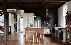The Byron Bay Home of Anna and Andrew Swain and their family. Above – kitchen and living area. French armoire pantry and factory pigeon holes in hallway. Production – Lucy Feagins / The Design Files. Rustic Kitchen, Kitchen Dining, Loft Kitchen, Warehouse Kitchen, Kitchen Stools, Open Kitchen, Luxury Kitchens, Cool Kitchens, Traditional Kitchen Inspiration