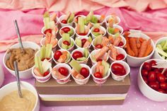 A bite size vegetable spread . Using baby versions of the veggies they fit snugly in small candy cups. Multiple dips were ready beside them for dipping.