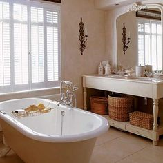 lovely traditional bathroom, clawfoot tub, double sink vanity, antique mirror, baskets