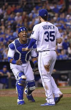 Kansas City Royals catcher Salvador Perez (13) gives first baseman Eric Hosmer (35) a big smile after Hosmer caught a pop foul for an out on Toronto Blue Jays' Russell Martin to end the top of the sixth inning during Friday's baseball game on July 10, 2015 at Kauffman Stadium in Kansas City, Mo.