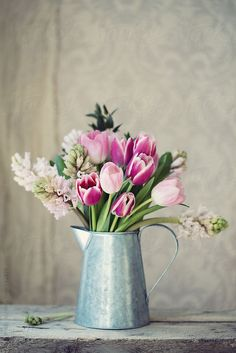 Spring flowers in a tin jug by RuthBlack   Stocksy United