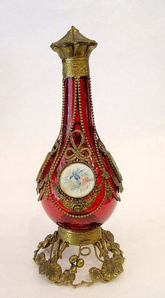 Tall Palais Royal Ruby Red scent Bottlewith 4 Miniatures of Flowers Painted on Ivory.  Fine Dore Bronze Mounts depicting Leaves and Flowers  SIZE: 10 1/2 inches HIGH  $750 USD SOLD