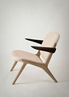 Love the outreaching darker arms on this wood and leather chair