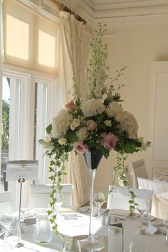 Martini Vase design topped with Delphiniums, Roses and Hydrangeas