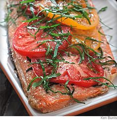 "Grilled Salmon With Tomato and Basil  2 cloves garlic, minced 1 teaspoon kosher salt, divided 1 tablespoon extra-virgin olive oil 1 whole wild salmon fillet, also called a ""side of salmon, about 1 1/2 pounds 1/3 cup fresh basil, plus 1/4 cup, thinly sliced, divided 2 medium tomatoes, thinly sliced 1/4 teaspoon freshly ground pepper Instructions Step 1 Preheat grill to medium. Step 2 Mash minced garlic and 3/4 teaspoon salt on a cutting board with the side of a chef's knife or a spoon"