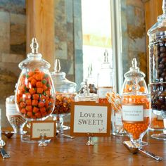 """A """"Love is Sweet"""" sign hung the treats table topped with old-fashioned mason jars. Inside the jars were swizzle sticks, licorice, mallow-crème pumpkins and whoppers (the groom's favorite!)"""