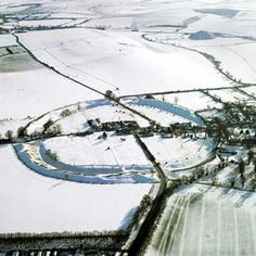 Striking aerial photo of Avebury Henge and Silbury Hill,blanketed with snow. Built between about 2,850 - 2,200 BCE, Avebury Henge is a 1/4 mile in diameter, the circumference a mile around, covering an area of 28 acres.  Silbury Hill is the largest artificial mound in Europe.