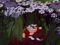 Dinah, from Alice in Wonderland, playing with a flower.