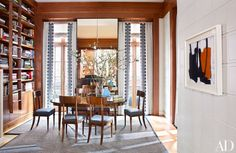 A Perle Fine painting hangs in the oak-paneled dining room; the wing chair is by Josef Hoffmann, and the Steinway piano is a family heirloom.