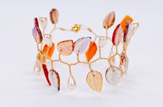 Robin Goodfellow Designs | Booth 652 | February 2014 http://www.robingoodfellowdesigns.com/ http://www.sfigf.com/ Hand-twisted glass leaves and crystals on gold-plated wire creates our beautiful bracelet. Magnetic closure 7.5 inches.