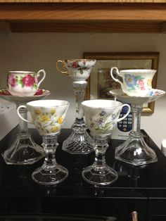 Tea cup candle holders :) - wonder if upside down wine glasses would work? Flowers in cups with tall taper in oasis too? too much?