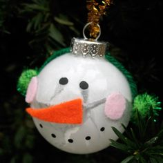 "Purchase white glass ornaments; glue 4"" green yarn across top; glue green pom-poms for ear muffs; cut & glue (2-small pink circles for cheeks) & (1-orange triangle for nose); paint eyes & mouth (black acrylic paint). Design & photo from Family Fun"