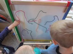 Contact paper (sticky side out) on easel.  Paper strips and yarn for a fun activity.