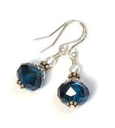 These earrings were handmade with teal blue crystal rondelles accented with silver plated beads and white glass pearls. They hang on sterling