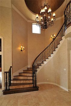 *Staircase* Handcrafted wood stairs with travertine risers and heavy-gauge iron spindles.
