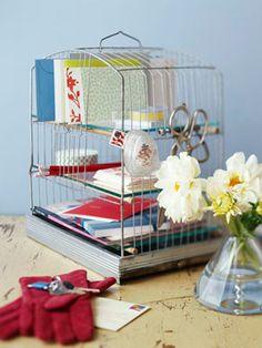 Ideia bacana pra organizar seus blocos de notas e cadernos: estante em gaiola! Isso mesmo, reutilize uma gaiola de passarinho e dê um toque charmoso à sua decoração :)