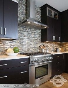 This kitchen backsplash has hints of green to complement the rest of the home's decor.  The hood and kitchen tile backsplash make a stunning focal point!