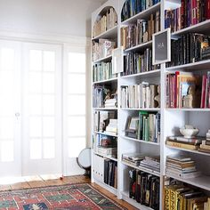 Amy's home office with customized Ikea shelves. I'm always envious of her book collection. #books #bookshelves #library #design #ikea | DesignSponge