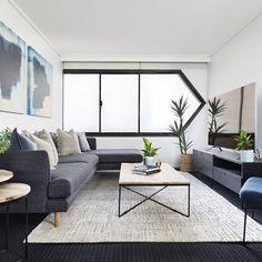 dark coastal living room with dark grey carpet and black window frames