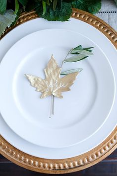 """Unique name cards for a Thanksgiving table: """"a quick coat of metallic gold spray paint can transform any simple object into a fancy décor piece. Finish off each leaf with a delicately scripted name in white pen."""" Photo: Becky Kimball. """"2 Easy DIYs for the Thanksgiving Table"""" by Megan Bailey. Pottery Barn Kids blog (November 12, 2014)."""