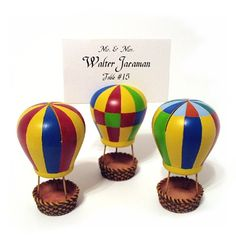 """These adorable Hot Air Balloon placecard holders are the perfect way to display your place cards as well as putting a couple of candies in the balloon's basket if you desire. Each place card holder is made of poly resin and comes in 3 assorted designs. Each place card holder measures 1 3/4"""" x 3"""" and holds a 2"""" x 3"""" placecard or photo. #weddingfavor #placecard #hotair @balloon"""