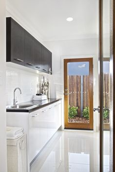 Clarendon Homes. Crestmead 46. Dual toned laundry with wooden trim door and see through glass panel.