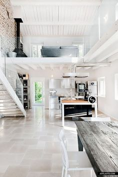 Exposed brick, glass railing, wood table, kitchen island.. Everything about this is perfect