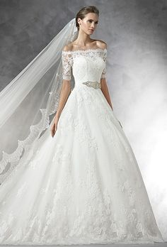 Brides: Pronovias. 'Primosa': Lace and petit pois tulle bodice. Off-the-shoulder neckline with lace scalloped edge and elbow-length sleeves.'Pranai': Petit pois and lace princess skirt with a scalloped edge.
