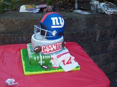 This was for a football themed birthday party for a NY Giants fan.  The bottom is a 12 square chocolate cake, the middle is a 10 vanilla cake, and the helmet is vanilla also.  1st time trying to make a helmet, wished I did a couple things different.  Thanks to everyones notes on their helmets.